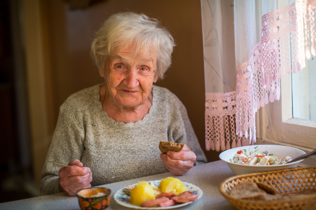 Elderly lady eating at her table